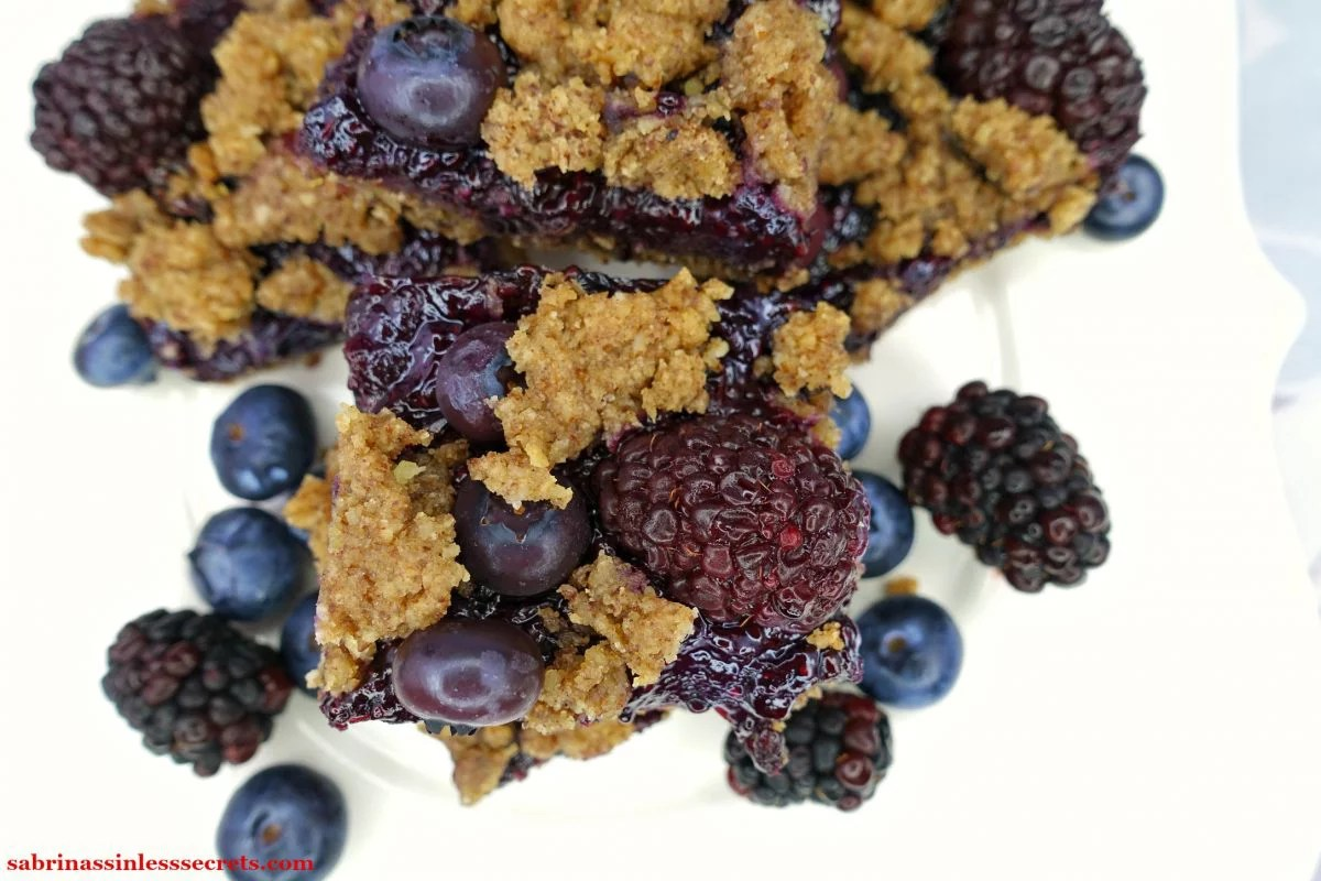 A stack of Black & Blueberry Gluten-Free Crumble Bars from the top view on a white plate