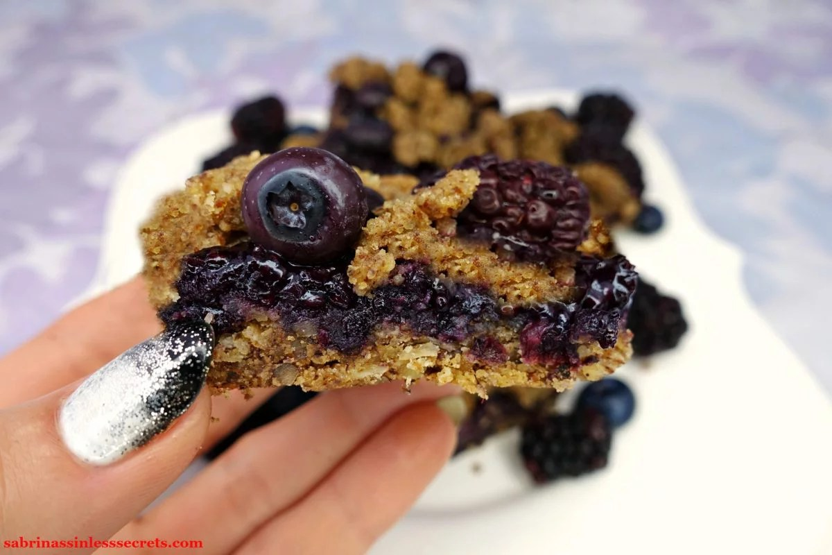 A Black & Blueberry Gluten-Free Crumble Bar held up by a hand with a white plate in the background with more bars