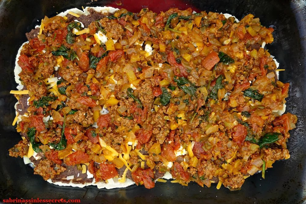 "A beef and vegetable mixture over ""refried"" black beans, cheddar, Parmesan, and mozzarella cheese, and Easy Paleo Tortillas in a glass 9x13-inch pyrex baking dish"