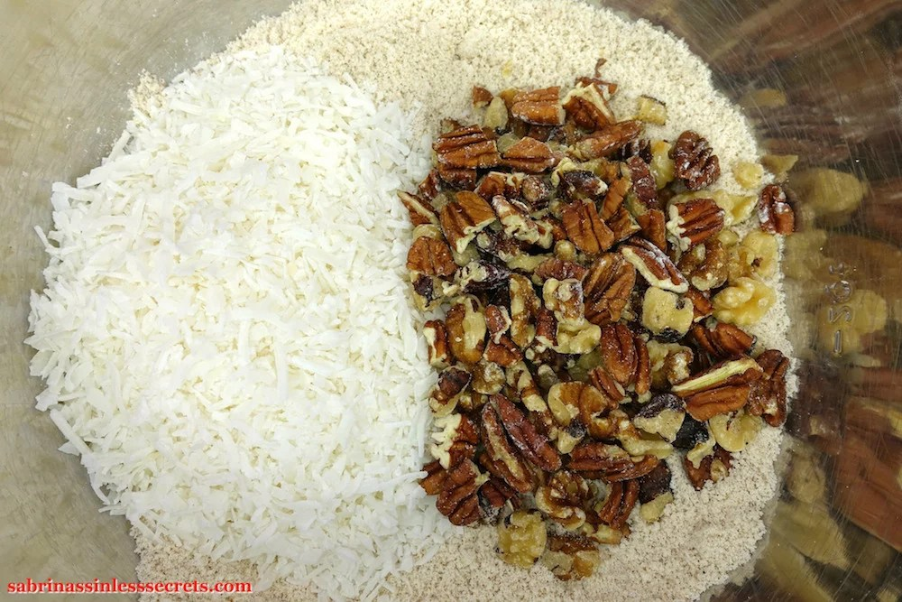 Unsweetened coconut flakes and chopped pecans and walnuts on top of the dry ingredients for Paleo Carrot Cake with Paleo Vanilla Bean Cream Frosting in a large stainless steel mixing bowl