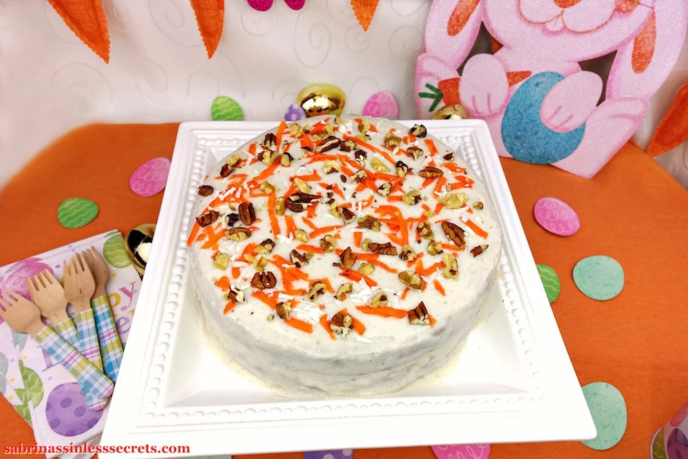 A Paleo Carrot Cake with Paleo Vanilla Bean Cream Frosting on a white square serving platter with an Easter egg bunny decoration, decorative carrots, and sparkly Easter eggs in the background