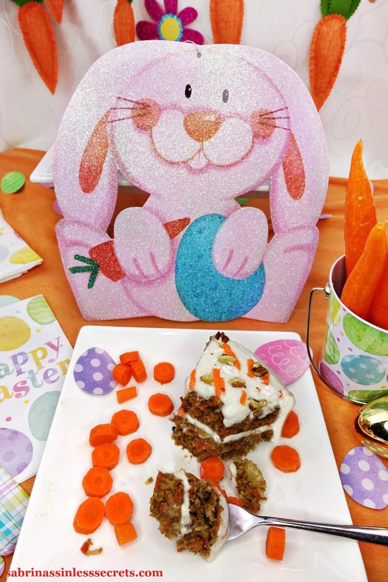 A piece of homemade Paleo Carrot Cake with Paleo Vanilla Bean Cream Frosting on a white plate with fresh carrot slices surround it and a decorative Easter bunny, Easter eggs, a can full of fresh carrots, and Easter napkins in the background