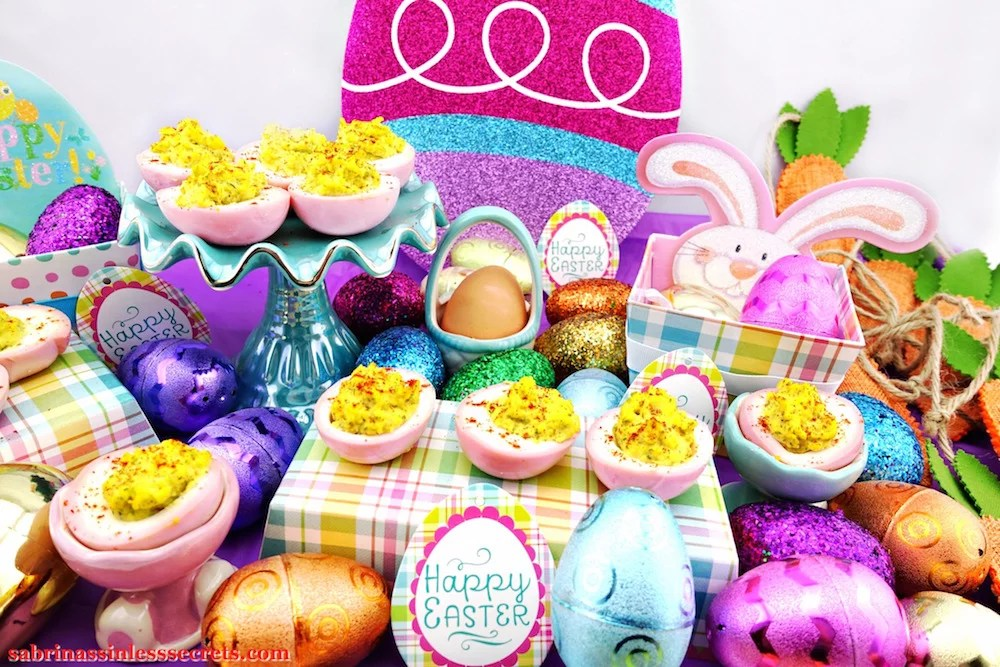 An arrangement of Pink & Paleo Deviled Eggs with Easter decorations of sparkly eggs, boxes, and eggs around them