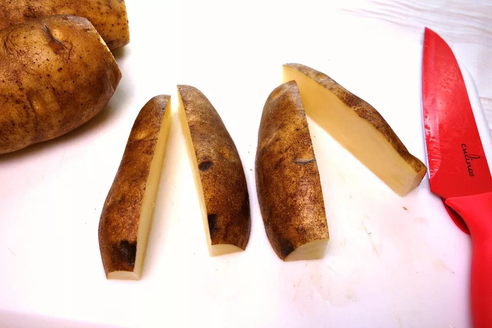 Two washed russet potatoes with the ends cut off and cut in half on a white cutting board with a red knife next to them