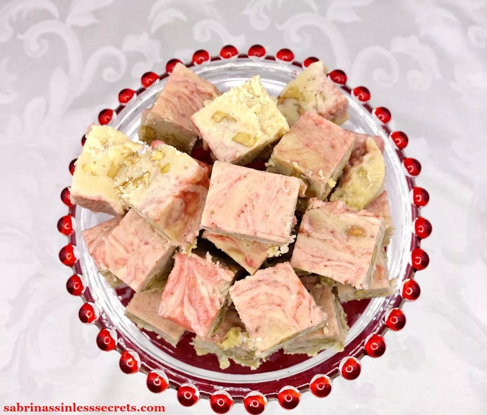 An overhead view of a mountain of Paleo and Vegan Strawberry Swirl White Chocolate Walnut Fudge on a clear class platter with glass red balls along the perimeter on a white damask tablecloth