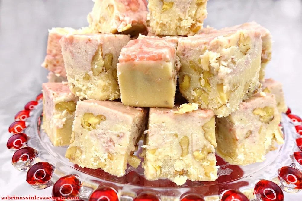 A mountain of Paleo and Vegan Strawberry Swirl White Chocolate Walnut Fudge on a clear glass platter with red balls on the perimeter and a white background