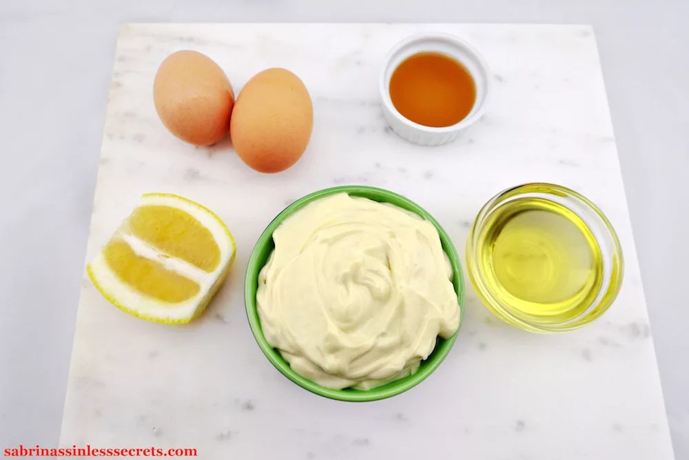 Homemade Paleo Mayonnaise in a green bowl with a side of avocado oil, a lemon slice, a cup of apple cider vinegar, and two large organic brown eggs surrounding it on a white marble background