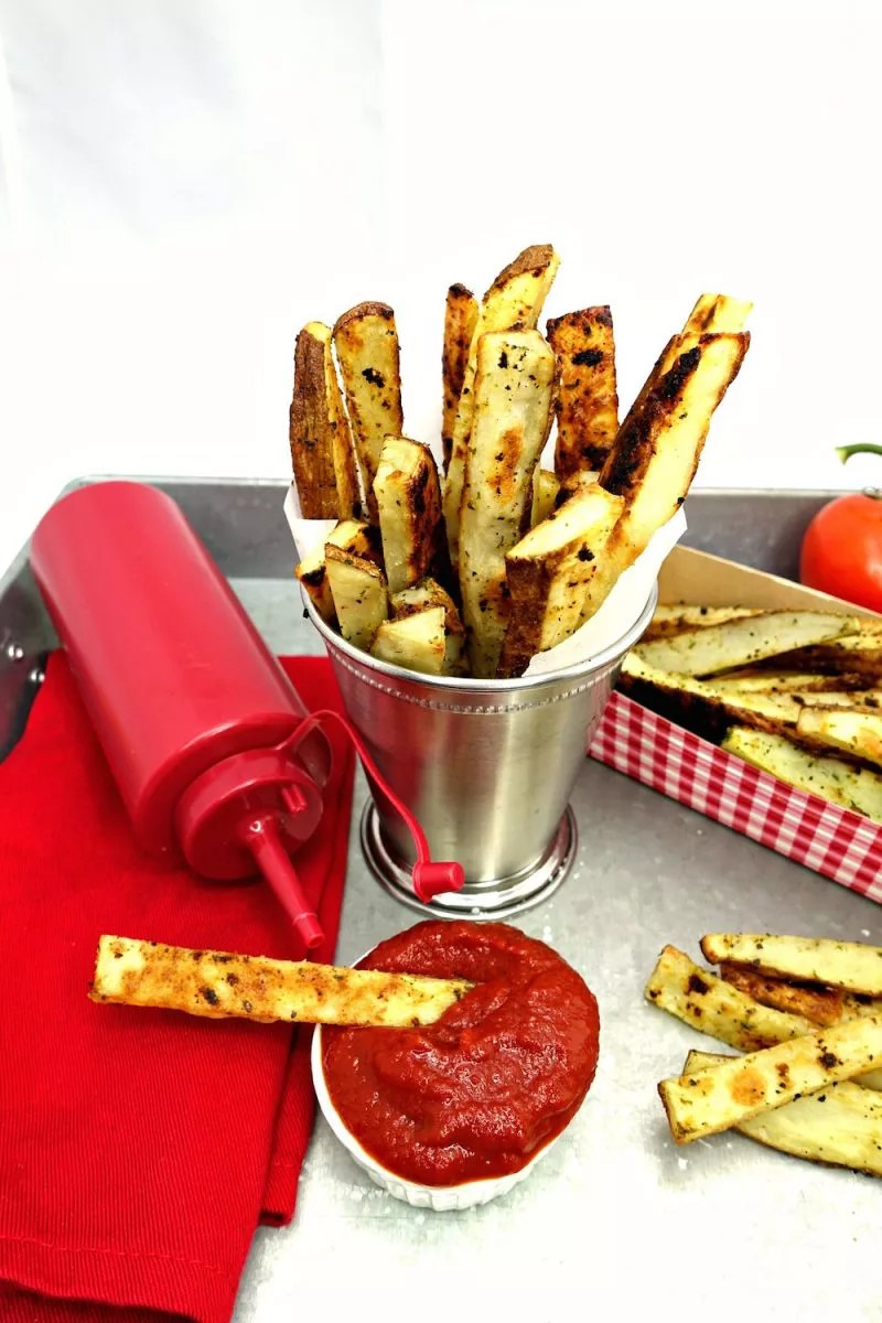 Seasoned Oven Baked Crispy French Fries sprouting out of a stainless steel cup with a small white side cup of homemade Quick and Easy Paleo Ketchup with a French fry in it and a red cloth napkin with a plastic red ketchup bottle on top of it adjacent to them