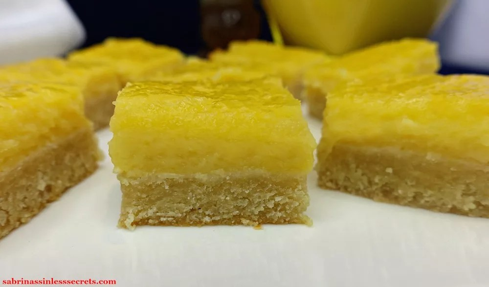 An up-close, side view of homemade A plate of homemade Paleo Lemon Bars with a Shortbread Crust on a white plate