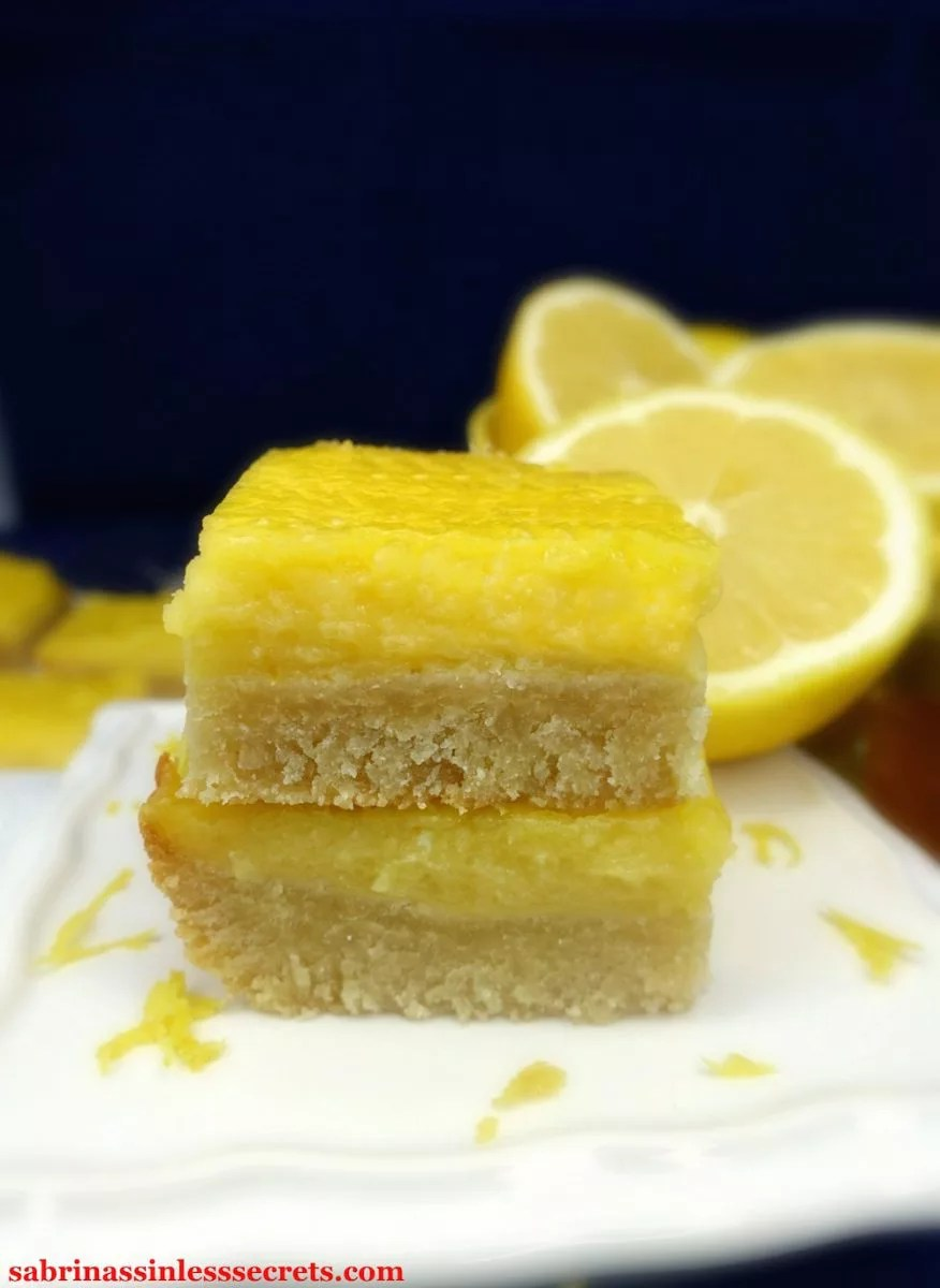 Two stacked homemade Paleo Lemon Bars with a Shortbread Crust on a small, white, square serving dish with fresh lemon zest and half-cut lemon on the side