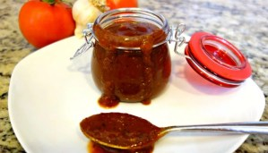 Easy Paleo BBQ Sauce in a small jar with a red latch lid on a white plate with a spoon full of Easy Paleo BBQ Sauce in front of it and whole tomatoes and whole garlic in the granite background