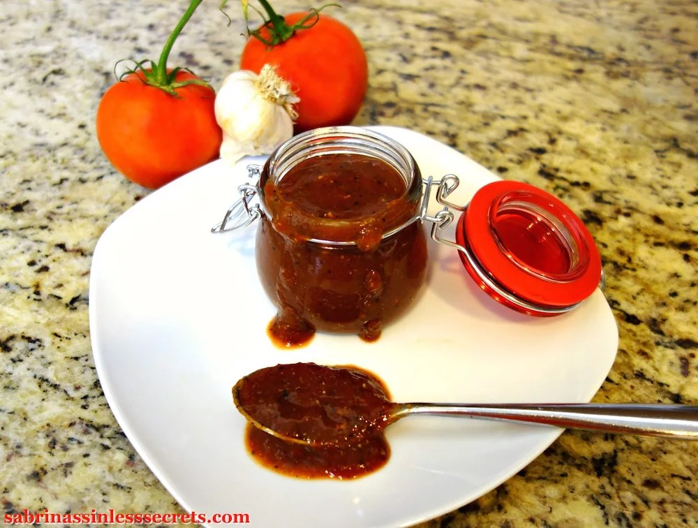 Easy Paleo BBQ Sauce in a jar with a red latch lid with BBQ sauce dripping down it on a white plate with a spoonful of more Easy Paleo BBQ Sauce and whole tomatoes and garlic in the granite background