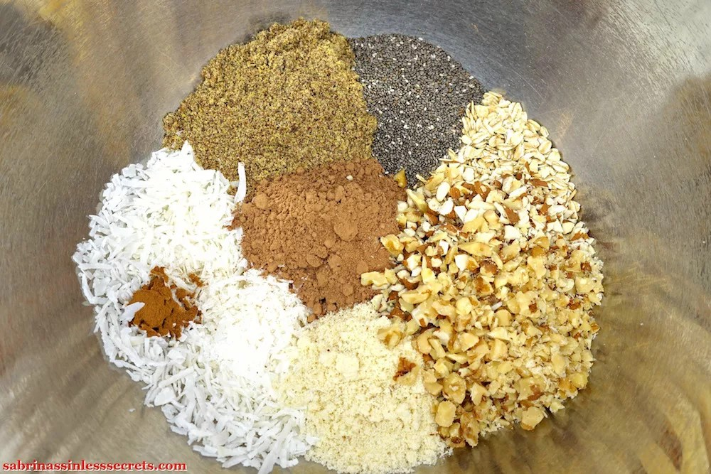 The dry ingredients for Gluten-Free and Vegan No-Bake Chocolate Chunk Almond Coconut Energy Balls in a large stainless steel bowl