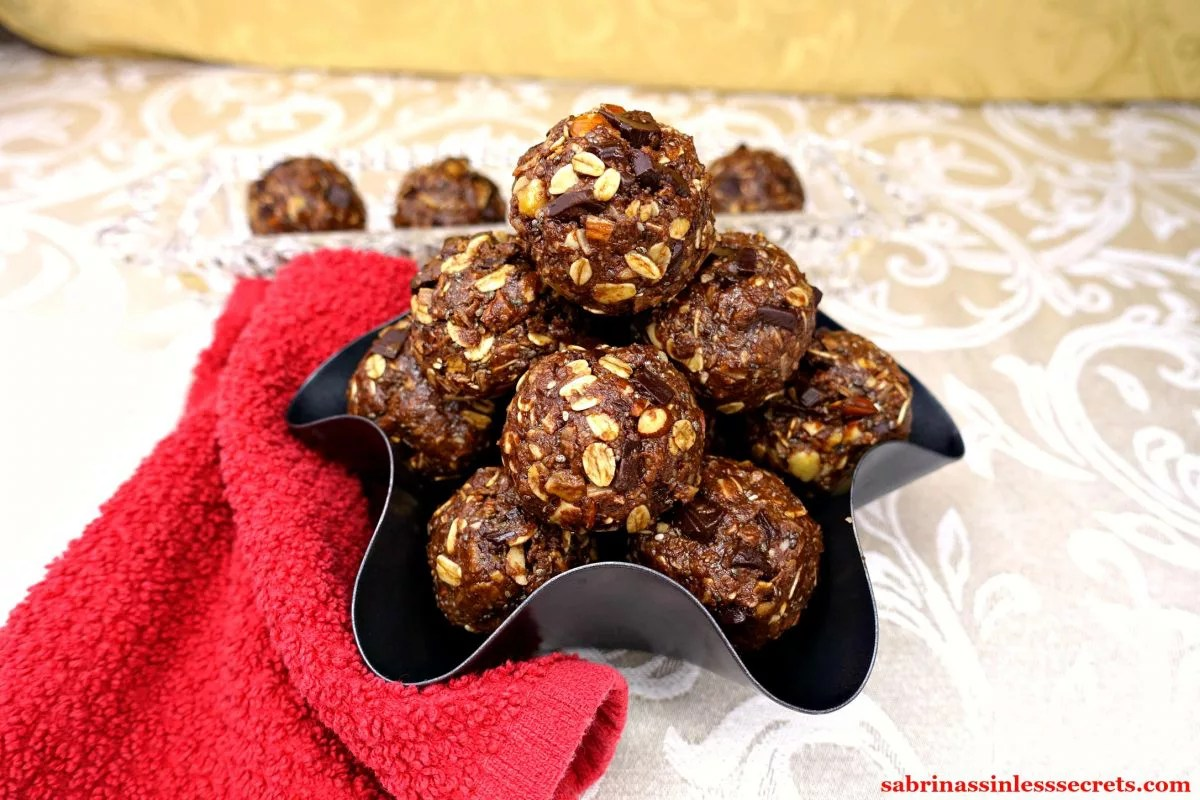 A mountain of Gluten-Free and Vegan No-Bake Chocolate Chunk Almond Coconut Energy Balls in a curvy, charcoal colored bowl with a red towel around it atop a white, damask background