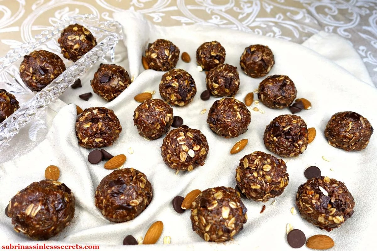 Gluten-Free and Vegan No-Bake Chocolate Chunk Almond Coconut Energy Balls scattered over a cream colored napkin with whole almond, dark chocolate chips, and oats around them with the addition of more Gluten-Free and Vegan No-Bake Chocolate Chunk Almond Coconut Energy Balls in a crystal tray alongside them