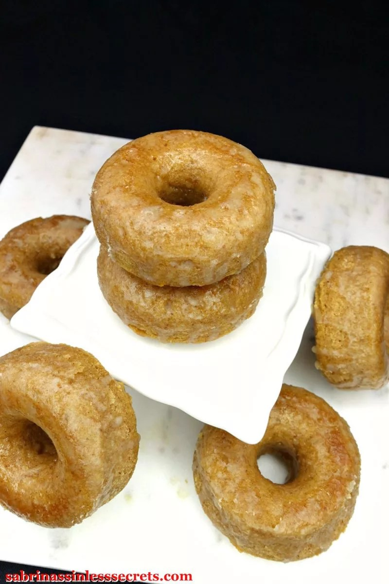 Two Paleo Maple Glazed Baked Donuts stacked on a square, white serving platter on top of a white marble slab with more Paleo Maple Glazed Baked Donuts around them