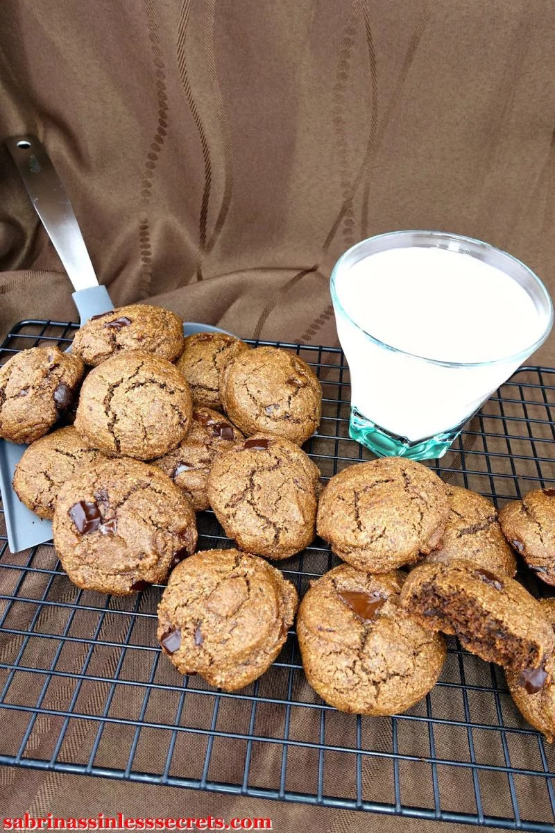 An assortment of Double Dark Chocolate Chunk Paleo Brownie Cookies on a cooling rack and cookie shovel with a glass of milk alongside them