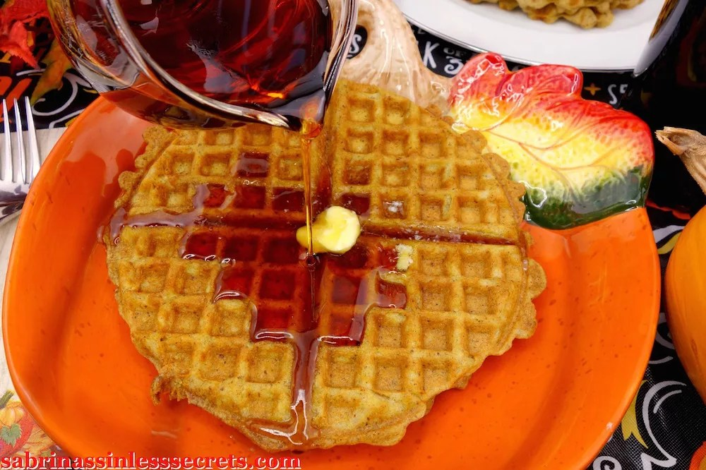 Plated paleo pumpkin waffles with butter and syrup pouring
