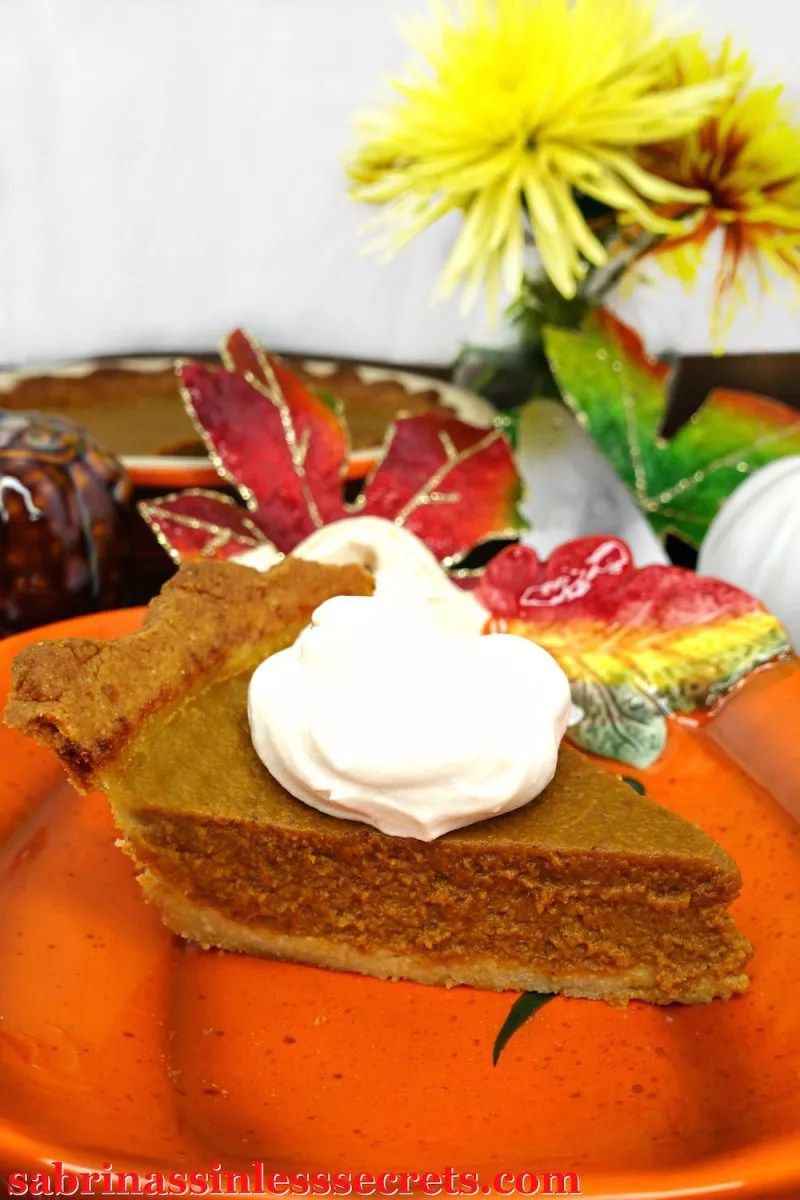 A single piece of paleo pumpkin pie sits with a large dollop of whipped cream