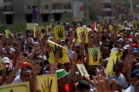 People raise their hands and banners to show a hand gesture of an open palm with four raised fingers during a protest in Beni Sueif, south of Cairo, Egypt, Friday, Aug. 30, 2013. The gesture became a symbol for the main sit-in of supporters of Egypt's ousted President Mohammed Morsi near the Rabaah al-Adawiya mosque in Cairo. The sit-in was violently disbanded.