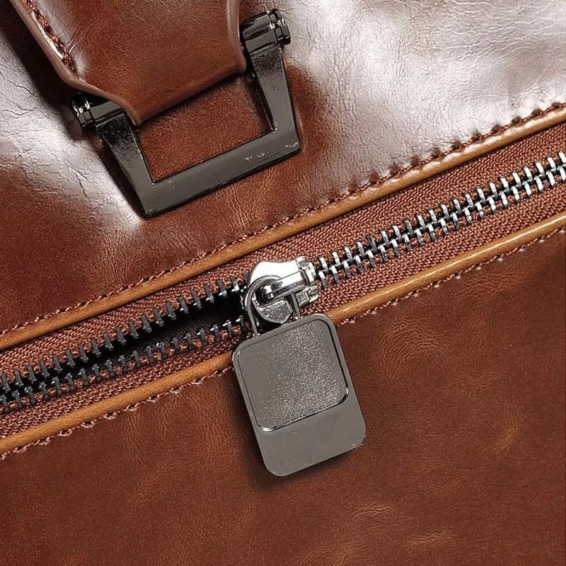 Détail fermeture à glissière et zip du sac porte-documents et ordinateur pour homme en cuir marron.