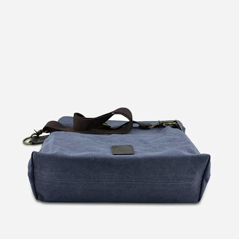 Dessous du sac besace en toile de couleur bleu avec sa bandoulière brune. Sacoche avec fermeture à rabat façon plié.