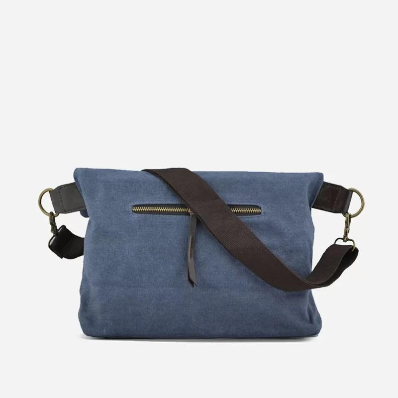 Verso du sac besace en toile de couleur bleu avec sa bandoulière brune. Sacoche avec fermeture à rabat façon plié.