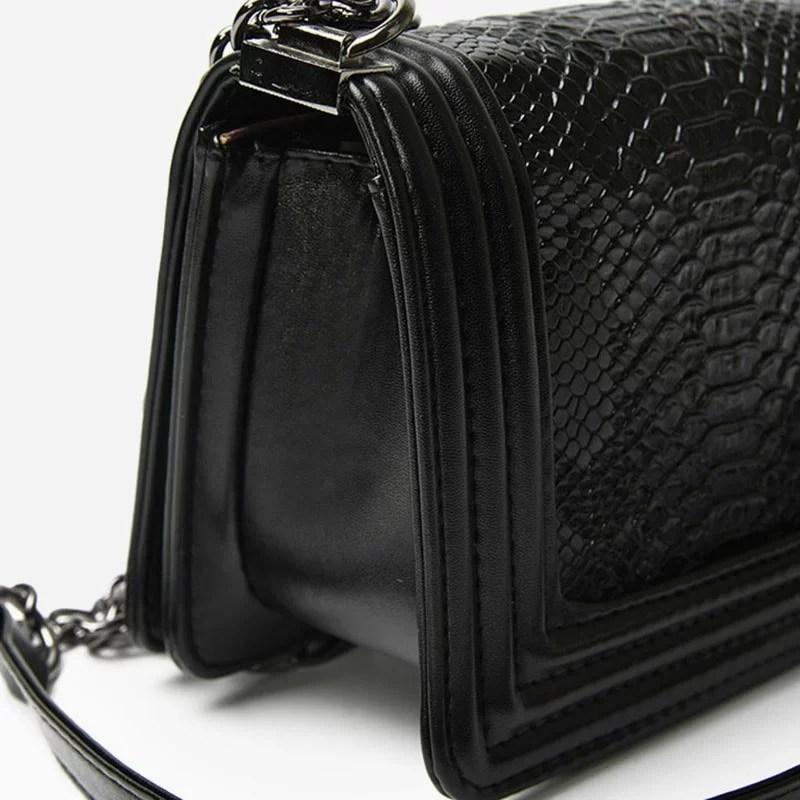 Détails du côté du sac besace pour femme avec bandoulière à chaîne et matière en cuir croco noir.
