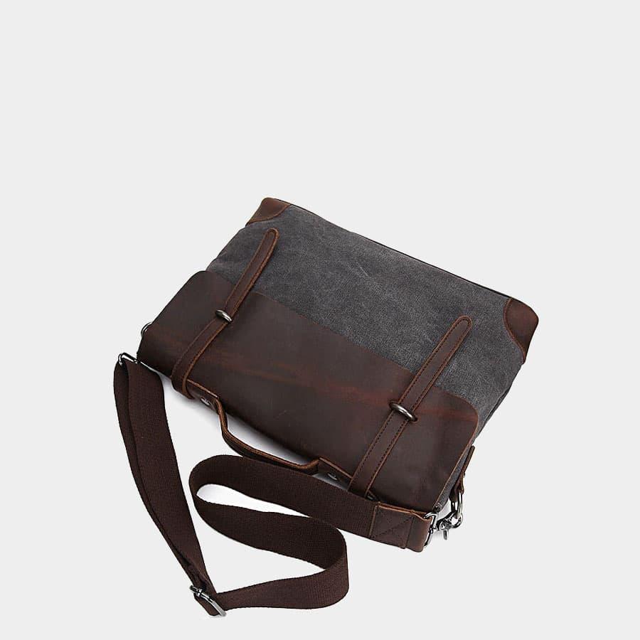 Sacoche bandoulière en toile noire et cuir véritable brun foncé.
