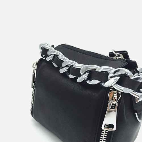 Détails des chaînes de l'anse et du cuir noir du sac à main.
