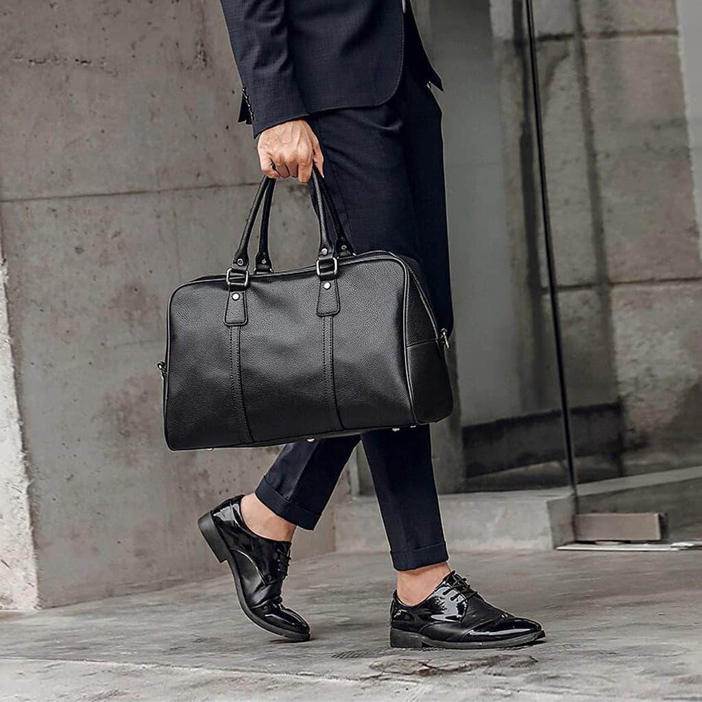 Sac de voyage 48h en cuir noir porté main avec un costume.