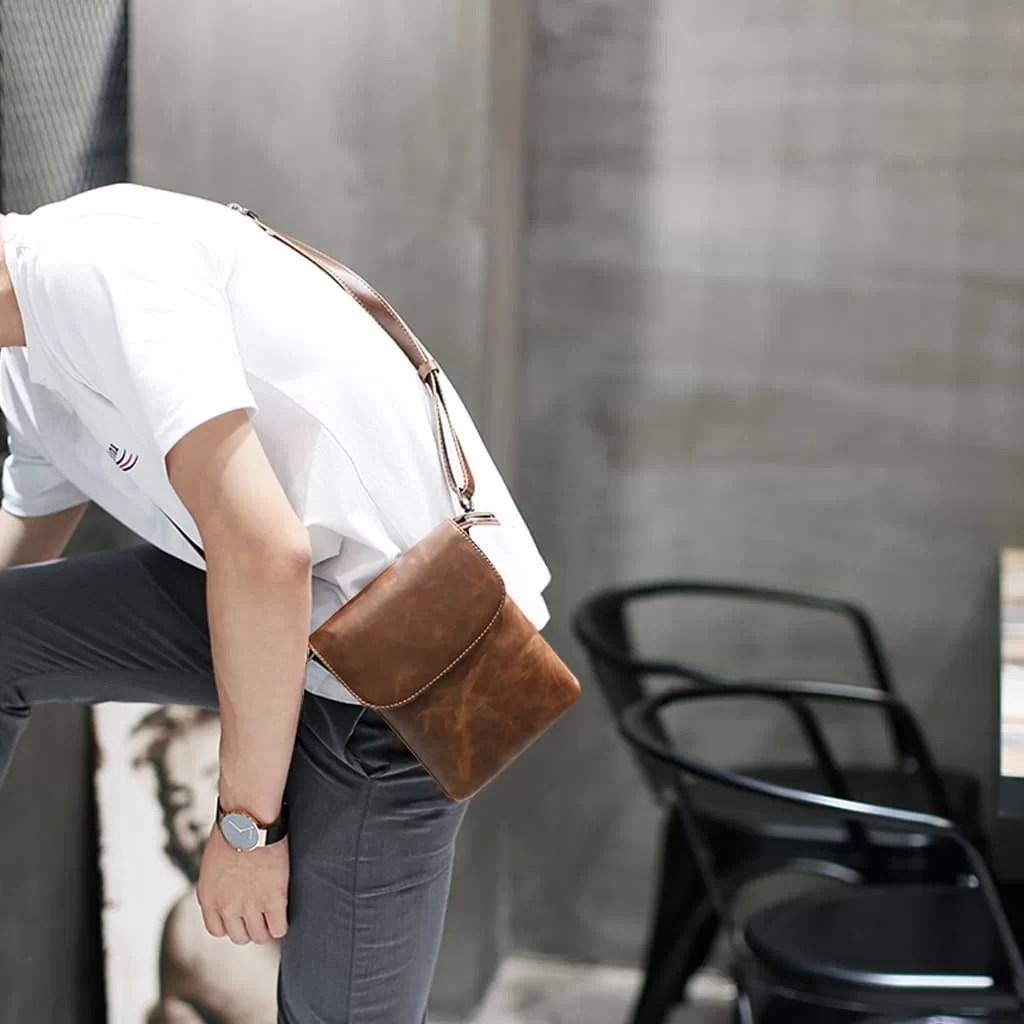 Petite sacoche besace reporter en cuir marron pour homme.