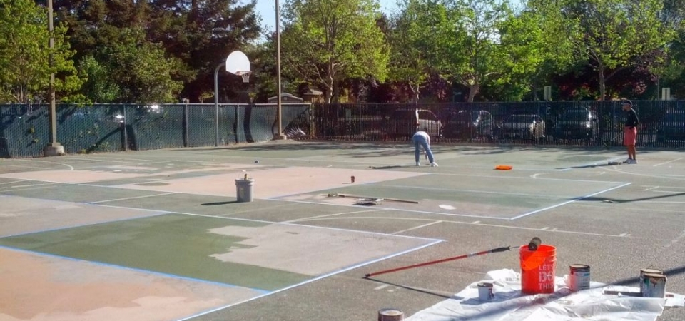 ACC Pickleball Court being painted by volunteers