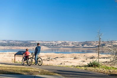 Cyclists viewing Folsom Lake at historic low levels during a major drought in California.