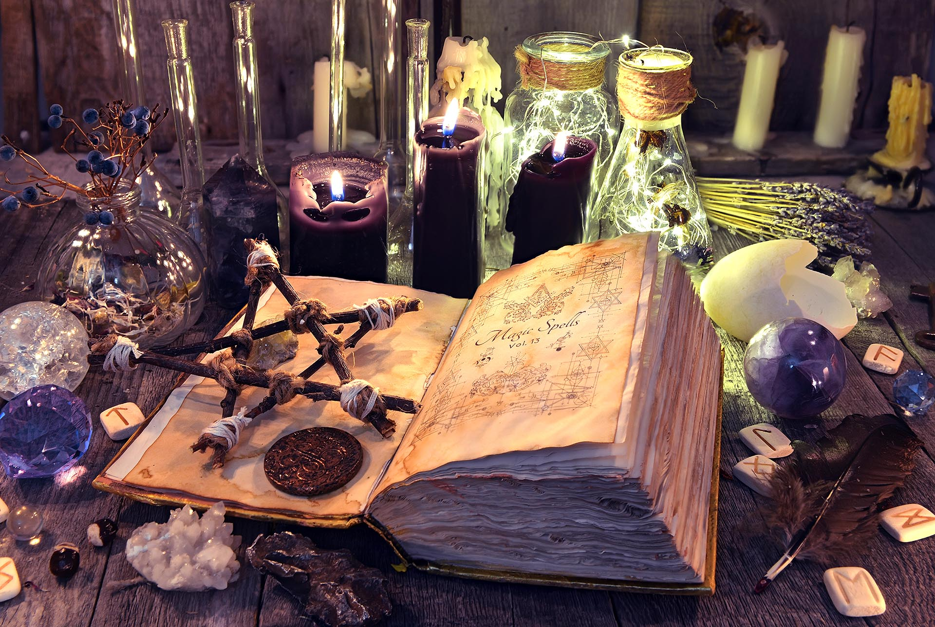 Magick spellbook with pentacle, candles and bottles