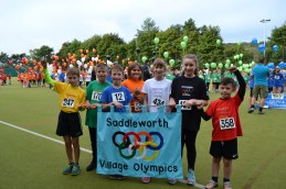 Children from each village with the new Olympics banner