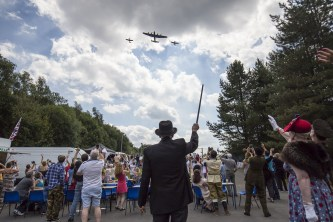 The crowd at Saddleworth School salute the passing aerial show