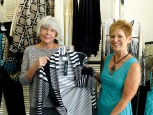 P.E.O. member Lorraine Erickson shows a lovely outfit to Fashion Show Chairman Dianne Ashby during their visit to Nadine's Desert Fashions; photo by Tammy Beeler.