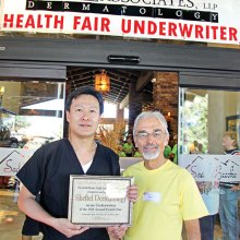 Ken Siarkiewicz, Health Fair Chair, presents a certificate thanking Sheftel Healthy Skin for underwriting the Health Fair.