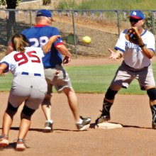 Janice Mihora flips the ball to Greg Morgan but it looks like runner Dale Norgard is safe.