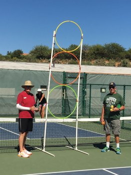 Karol Jackson tries her best to serve through the hoops. Gary Brunnelle and Terry Jackson monitor for accuracy; photo by Shawne Cryderman.