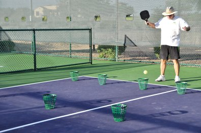 Mentor Bill Reynolds sets up baskets as targets on the court for his group to practice positioning the ball when they hit. undefined