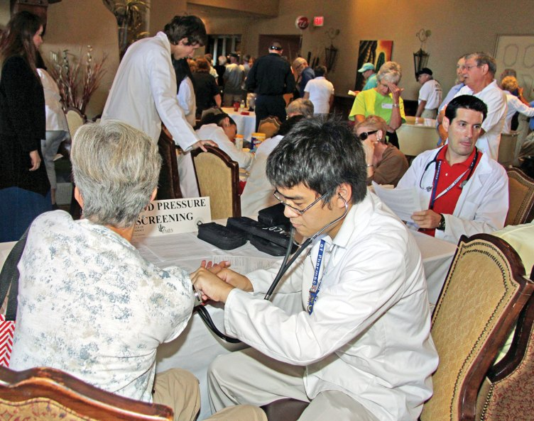 U of A Pharmacy student testing a SaddleBrooke resident at the Health Fair.
