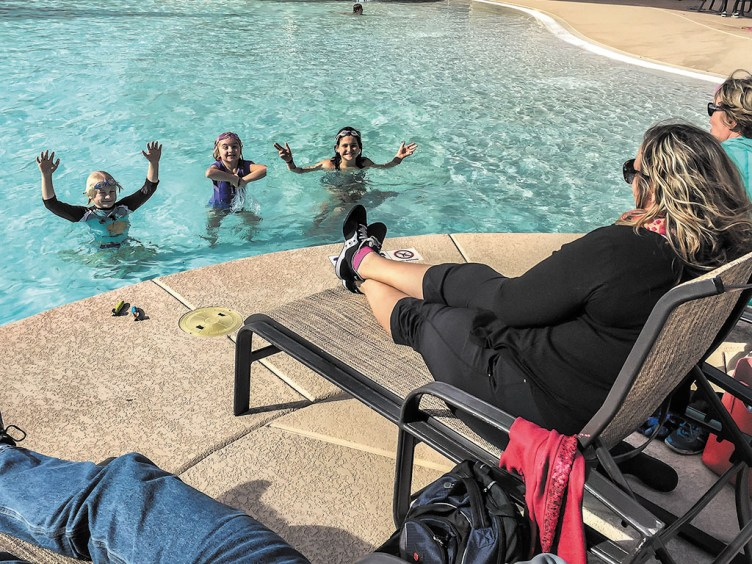 Grandchildren Bradley Olsson, Brooke Olsson, and Stella Gottlieb waving with thanks to Robson Communities for heating the pool while their parents and grandparents sit by the pool bundled against the cool wind.