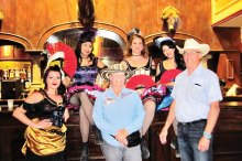 Toni McDole and Don Williams take a photo op with the Grand Hotel & Saloon dance hall girls.