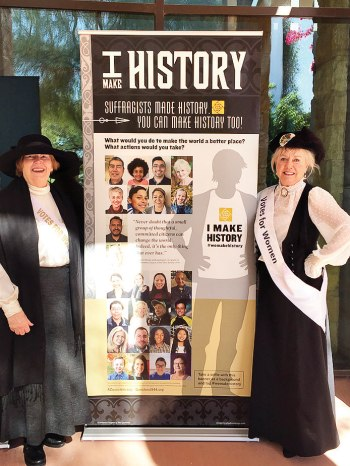 Questers Anne Levig and Debbie Hansen are dressed as suffragists beside the Questers Women's Suffrage Centennial Exhibit.