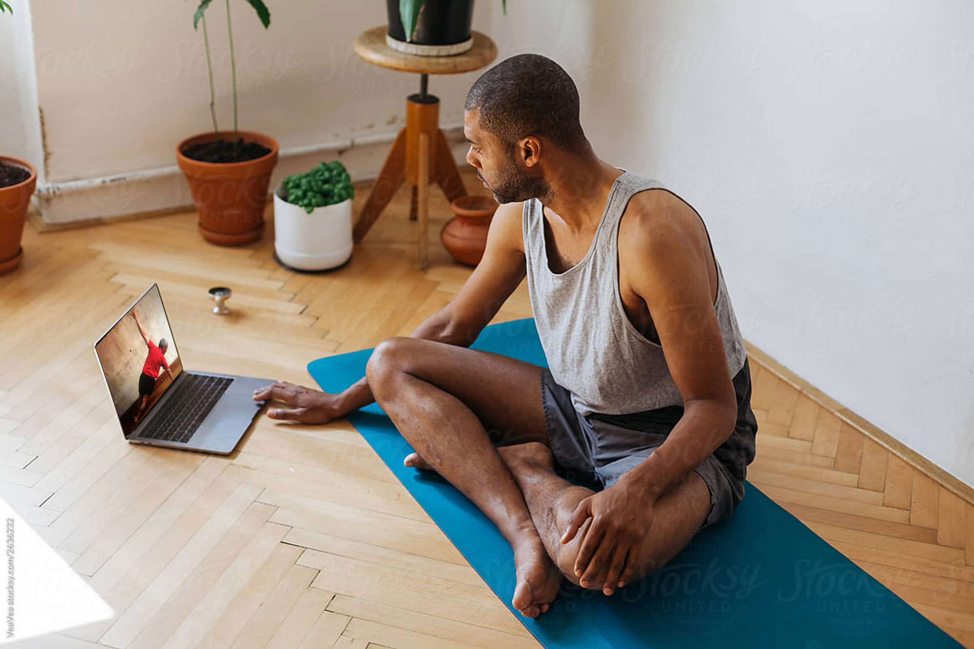 Man doing on demand yoga class at home
