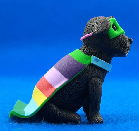 A colour photo of Millo doggeh in polymer clay wearing a rainbow coloured cloak