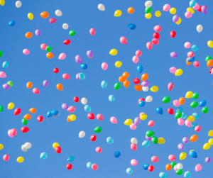 Several Different Colored Balloons Floating in the Sky