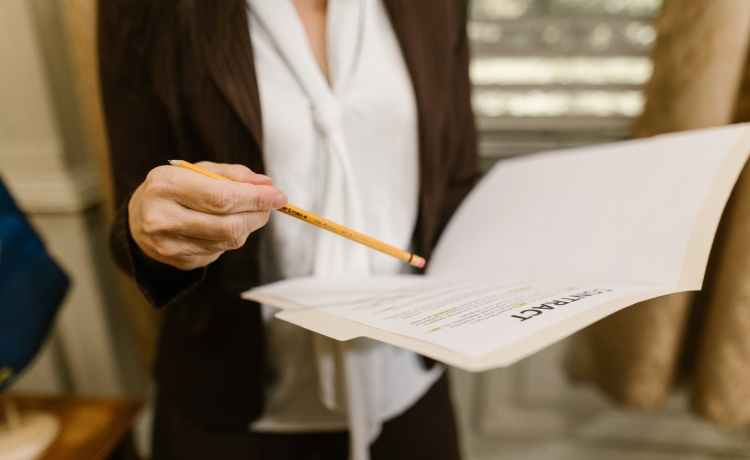 woman in white blazer writing on white paper